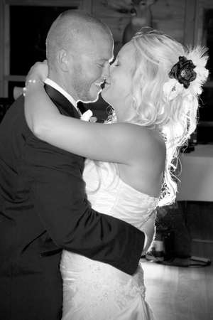 Happy young attractive newlyweds kissing black and white