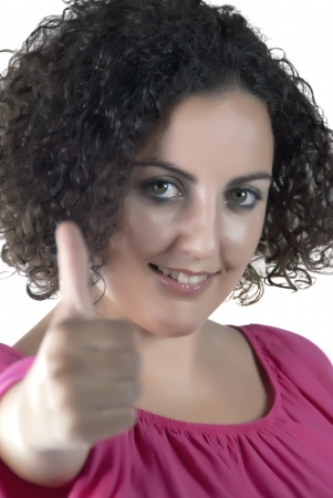 Portrait of beautiful woman with curly hair holding a thumbs up and smiling photo