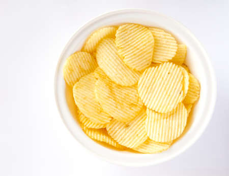 unhealthful: Potato chips in the white bowl on white background Stock Photo