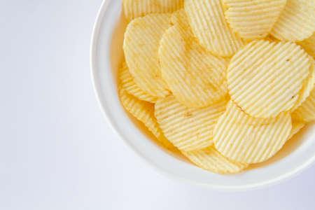 unhealthful: Potato chips in the white bowl on white background Stock Photo