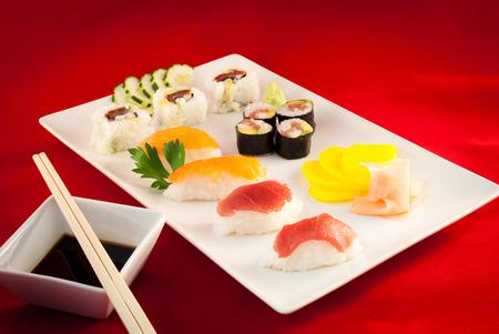 atun rojo: Variada Sushi de atún rojo pescado con los palillos en un plato. Fondo Rojo