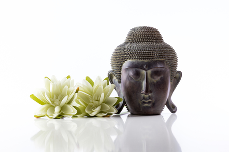 Isolated Buddha head on a white background with reflection and lotus