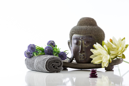 head stones: Buddha head above pedestal on a white background, towel, stones, flower and lotus with reflection Stock Photo