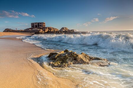 military invasion: Big military bunker and waves crashing on beach shore in Cadiz, Spain