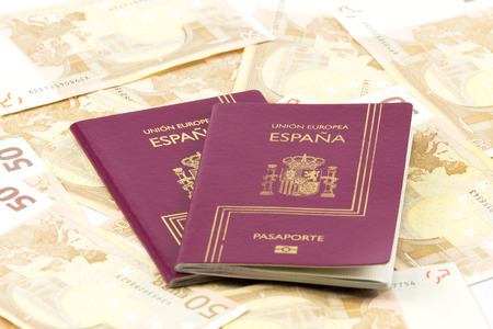 businesstrip: With Spanish passport european union currency banknotes as a background