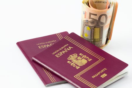 businesstrip: With Spanish passport european union currency banknotes on a white background