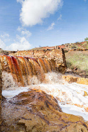 Waterfall in Riotinto mining area, Andalusia, Spain. The Rio Tinto Red River is a river in southwestern Spain.