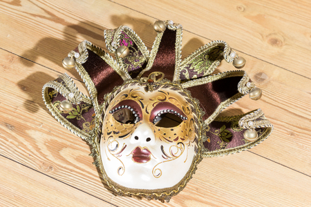 venician: Carnival Venetian mask isolated on wood background Stock Photo