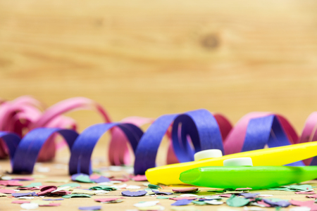 serpentinas: confetti, streamers and party whistle on wood background