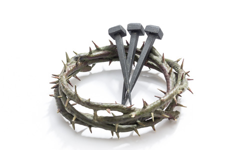 Jesus Christ crown of thorns and nails on a white background. Focus is on part of the nails. Imagens