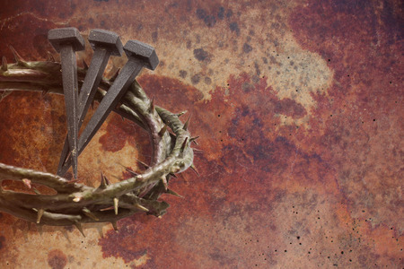 viacrucis: Jesus Christ crown of thorns and nails on a grunge background. Focus is on part of the nails. Stock Photo
