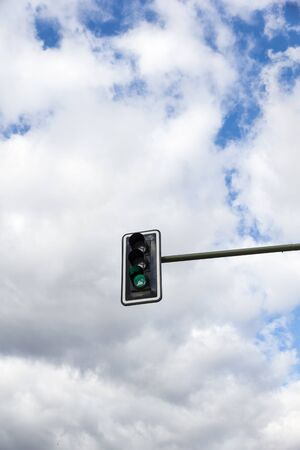 standstill: Image of traffic lights while green light on. Cloudy sky background Stock Photo