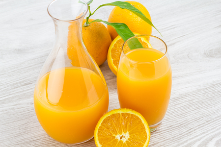 oranges and glass of juice on a wooden table. Closeup