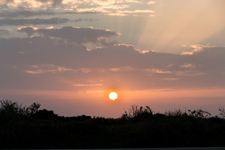 Sunset with clouds, light rays at Lagos, Algarve, Portugal Stock Photo