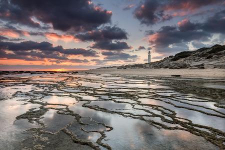 trafalgar: Sunset at Trafalgar beach, nearby lighthouse, where the great battle of Trafalgar took place. Costa de la Luz, Cadiz, Spain Stock Photo