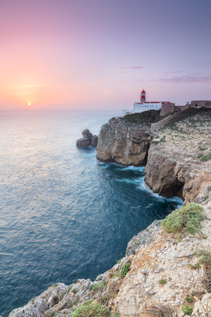 View of the lighthouse and cliffs at Cape St. Vincent at sunset. Continental Europes most South-western point, Sagres, Algarve, Portugal.