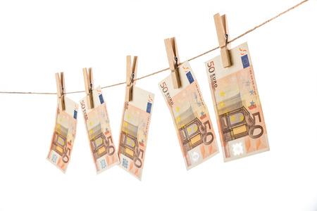 banconote euro: 50 euro banconote appesa clothesline su sfondo bianco. concetto di riciclaggio di denaro