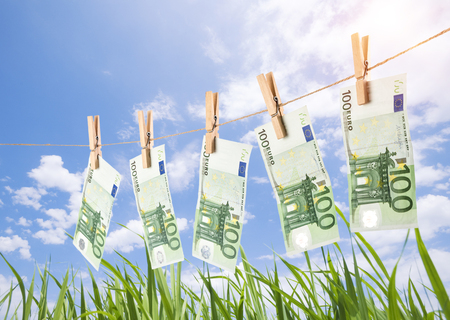 100 Euro banknotes hanging on clothesline on grassland background. Money laundering concept