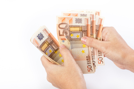 give out: Close up of female hand holding 50 euro banknotes isolated on white background Stock Photo