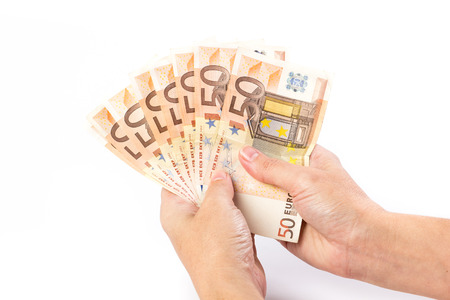 Close up of female hand holding 50 euro banknotes isolated on white background Stock Photo