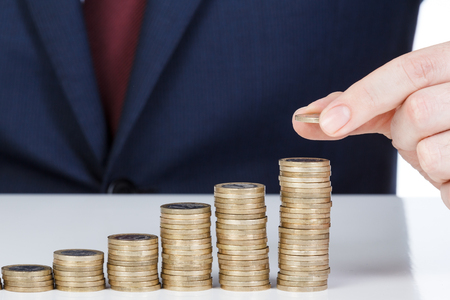Businessman hand stacking one euro coins into increasing columns. Financial concept. Closeup. Imagens