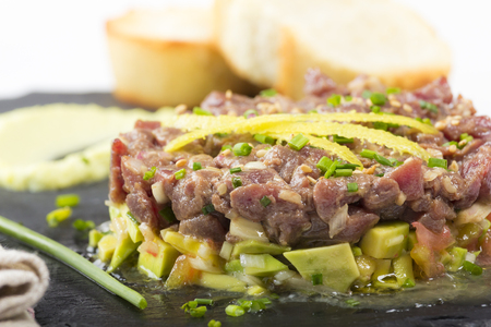 Bluefin tuna tartare on a black slate plate with avocado, served with grilled bread.