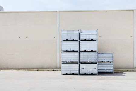 Stack of empty containers next to a warehouse in the fishing port of Barbate, Cádiz, Spain