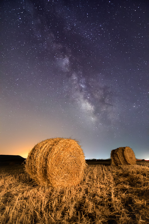The Milky Way shines bright over a straw bales. Long exposure with light painting. Imagens