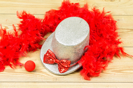 silver tall hat, red fluffy feather boa, red bow tie and red clown nose on wood background. Carnival accessory.