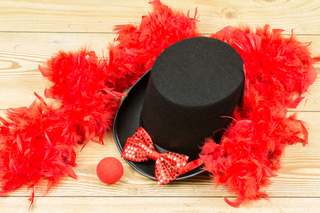 black tall hat, red fluffy feather boa, red bow tie and red clown nose on wood background. Carnival accessory. Imagens