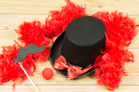 black tall hat, red fluffy feather boa, red bow tie and red clown nose on wood background. Carnival accessory. Imagens - 92874823