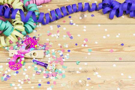 confetti, streamers, mask and party blower on wood background