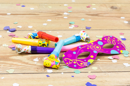 confetti, mask and party blowers on wood background