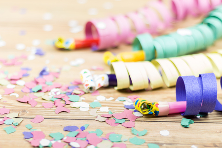 confetti, streamers and party blower on wood background
