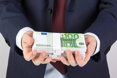 Businessmans hand holding money, euro banknotes. Financials, investment success and profitable business concept. Imagens
