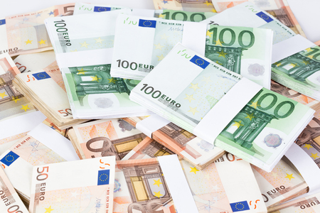 Pile of fifty and one hundred euro banknotes on white background
