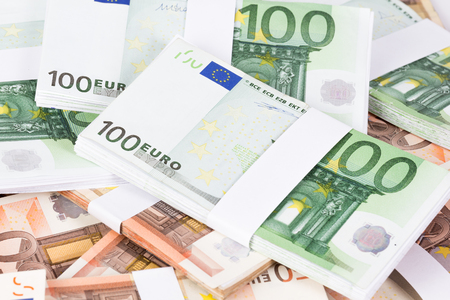 Closeup pile of fifty and one hundred euro banknotes on white background