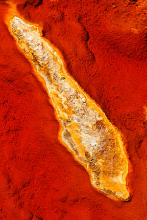 Abstract textures and formations on the banks of Rio Tinto river, Andalusia Spain. Shades of red and orange, iron and other minerals in the water.