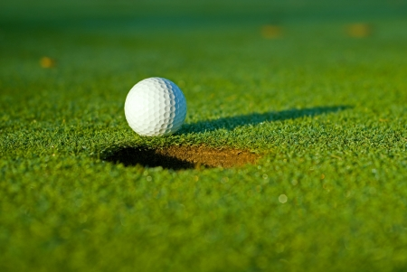 White golf ball on putting green next to hole with long shadow and selective focus on ball.  Stock Photo