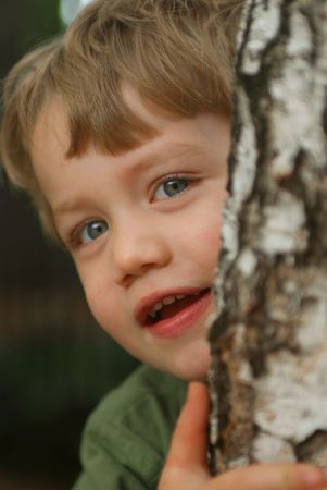 Young boy toddler peeking out from behind tree Stock Photo - 2340245