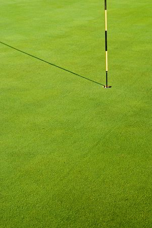 Striped golf flag in green hole with morning shadow on grass Stock Photo - 3028347