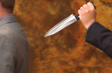 Businessman being stabbed in the back by traitor colleague or partner Stock Photo