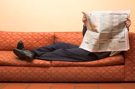 Businessman reading newspaper whilst waiting for appointment corporate office and lying on sofa Stock Photo