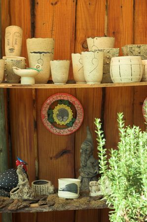 nurseries: Nursery scene with earthen pots on wooden wall and green plant in front Stock Photo