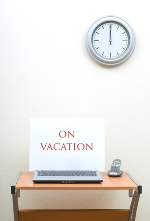 Laptop With On Vacation Sign Next To Portable Phone Top Of Office Desk Clock