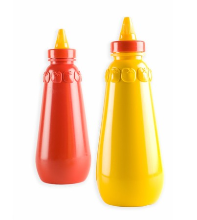 Mustard and tomato ketchup bottles - selective focus on mustard bottle Stock Photo