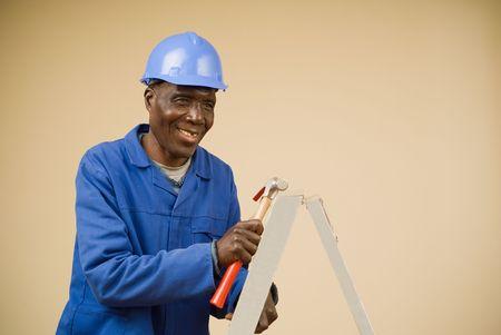 Construction worker climbing ladder holding hammer, carpenter, handyman photo