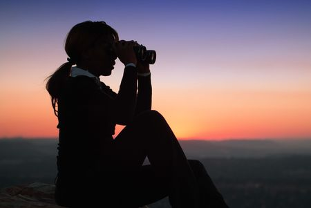 african american silhouette: Silhouette of Business Woman with Binoculars Sitting on a Hilltop