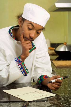 Close Up of Young African American Chef Writing Shopping List  photo
