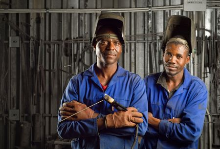 factory workers: South African or American black workers or welders in factory Stock Photo